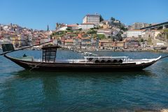 Traditional Rabelo Boat on the Bank of the River Douro and Colorful Facades of Typical Houses- Porto, Portugal Royalty Free Stock Photography
