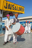 Traditional rajasthani musicians posing for photo under the big Jaisalmer sign on railway station. Royalty Free Stock Images