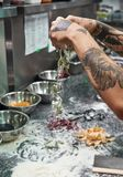 Traditional recipe. Cropped vertical image of chef`s hands with beautiful tattoos making traditional italian pasta in. Restaurant kitchen. Food concept royalty free stock photo