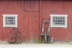 Traditional red barn wall, a window and a sled Stock Photos