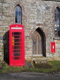 Traditional red British public telephone box containing a defibrillator unit, Dartmoor Royalty Free Stock Images
