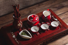 Traditional red chinese tea set, red porcelain with traditioanl chinese theatre masks. On the wood table stock image