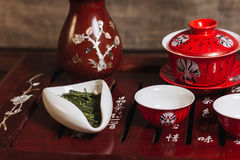 Traditional red chinese tea set, red porcelain with traditioanl chinese theatre masks Stock Photos