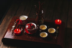 Traditional red chinese tea set, red porcelain with traditioanl chinese theatre masks. On the wood table royalty free stock photo