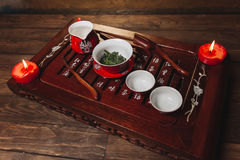 Traditional red chinese tea set, red porcelain with traditioanl chinese theatre masks. On the wood table with candles stock image