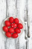 Red Easter eggs in plate on wood royalty free stock images