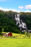 Red farm next to a waterfall. Stock Photo