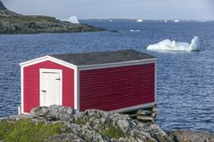 Red fishing stage on coast, icebergs in bay, Newfoundland royalty free stock image