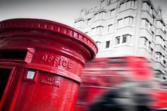 Traditional red mail letter box and red bus in motion in London, the UK. Stock Image