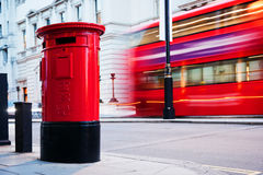Traditional red mail letter box and red bus in motion in London, the UK. Stock Photo