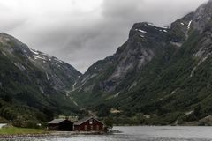Traditional red Norwegian house standing alone in. Traditional red Norwegian house standing alone in the fjord. Secluded village in the wild nature. Moody stock images