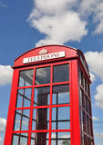 Iconic telephone box, blue sky, some clouds Royalty Free Stock Photo
