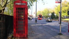 Traditional red telephone box, double decker London buses, Park Lane, Hyde Park, London, England stock video footage
