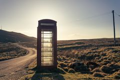 Traditional red telephone box standing by the side of the road Royalty Free Stock Image