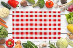 Traditional red white table cloth on kitchen table surrounded with vegetables.  Stock Image