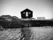 Traditional red and white wooden house on rocky island. Suny spring day with smooth water level in bay. Rural Norwegian landscape, traditional red and white Royalty Free Stock Photo