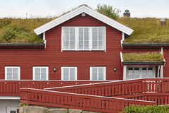 Traditional red wooden norwegian cabins with ground on the roof. Horizontal royalty free stock photography