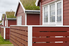 Traditional red wooden norwegian cabins with ground on the roof. Horizontal stock images