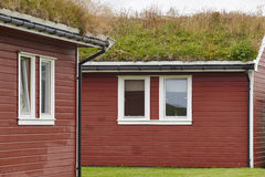 Traditional red wooden norwegian cabins with ground on the roof. Horizontal royalty free stock images