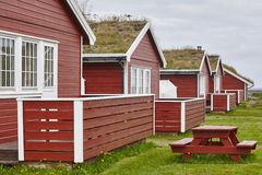 Traditional red wooden norwegian cabins with ground on the roof. Horizontal stock photo