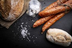 Traditional smoked sausage.  A portion of rural sausage on a chopping board. royalty free stock photography