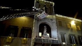 Traditional religious ceremony for the feast of the Immaculate Conception: floral tribute of the italian firemen. To the statue of the Madonna on the facade of stock footage