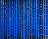 Retractable folding blue door gate Stock Image