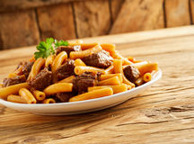 Traditional rigatoni noodles with lean beef cubes. Traditional Italian rigatoni noodles with lean beef cubes in a spicy sauce garnished with parsley in a tilted Stock Images