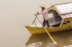Traditional river boat Kuching, Sarawak. KUCHING, SARAWAK - SEPTEMBER 24: Man rowing a traditional river boat transporting people across Sarawak River on Royalty Free Stock Photo