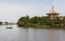 Traditional river boat Sarawak, Malaysia. KUCHING, SARAWAK - SEPTEMBER 24: Traditional river boat transporting people across Sarawak River with State Legislative stock image