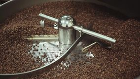 Traditional roaster machine mixing freshly roasted coffee beans at the local coffee shop. Close up view, slow motion. stock video footage