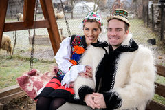 Traditional romanian clothing. Couple on a bench at the country side dressed in traditional clothes. The photo is taken in Maramures Romania stock photos