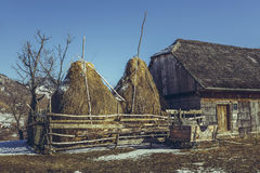 Traditional Romanian farm. Spring rural scene with traditional Romanian farm with wooden barn, haystacks and large sleigh in Magura village, Brasov county Stock Photography