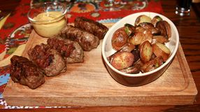 Traditional romanian food. Mici garnished with potatoes and mustard stock photos