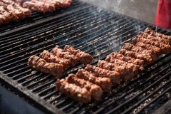 Meat balls called mici or mititei on grill Stock Photo