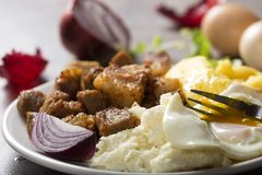 Traditional Romanian food `Tochitura Moldoveneasca`. Made with pork meat, egg and cheese with polenta on plate stock photography