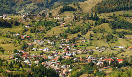 Traditional Romanian village. Pretty village in the Carpathian Mountains situated in a valley Stock Images