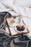 Traditional romantic breakfast in bed in white and beige bedroom Royalty Free Stock Photo