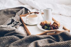 Traditional romantic breakfast in bed in white and beige bedroom Royalty Free Stock Image