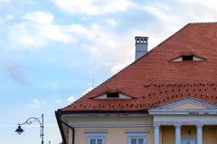 Traditional roof with small windows like eyes in Sibiu, Transylvania, Romania. Detailed architecture of a house top with columns royalty free stock photography