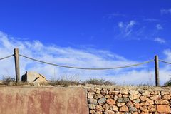 Traditional rope fence over stone wall grunge Stock Photo