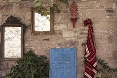 Traditional rug carpet and antique mirrors. Are hung on old stone wall in old town of Cunda Alibey island. Blue wooden door is leaned Stock Images