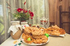 Table in rustic house, on which there are plates with buns, pies and pretzels, samovar, clay jugs with milk, and vase with bouquet. Traditional Russian baked Stock Photos