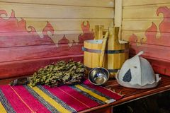 Traditional Russian bath equipment on the wooden bench. Wooden bucket, ladle, oak broom, bath hat and towel Stock Photo