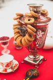 Traditional Russian brass painted samovar on a red tablecloth, a symbol of hospitality. Crispy bagels, drying or bagels hang on. The samovar. Blurred background stock photography