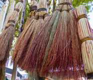 Traditional Russian brooms hang over the market counter.  Stock Photo