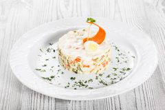 Traditional russian Christmas and New year salad Olivier with decoration on the plate on light wooden. Top view stock images