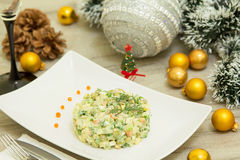 Traditional Russian christmas salad Olivier with sausage and fresh cucumbers. On a white plate Stock Photos