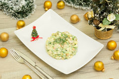 Traditional Russian christmas salad Olivier with sausage and fresh cucumbers. On a white plate Royalty Free Stock Photos