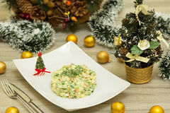 Traditional Russian christmas salad Olivier with sausage and fresh cucumbers. On a white plate Royalty Free Stock Images